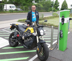 Olaf at a charging station with his Brammo.